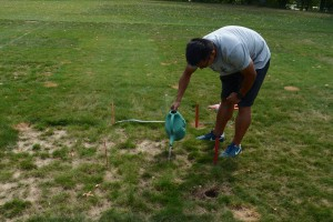 Eric Chen flushes fine fescue plots. The stakes indicate a 1 square yard area. Photo: Richard Buckley, Rutgers PDL